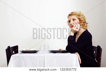 single woman sits besides the served table