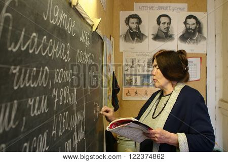Podol village Tver region Russia - May 5 2006: School teacher writes with chalk on the blackboard in the classroom of rural school.