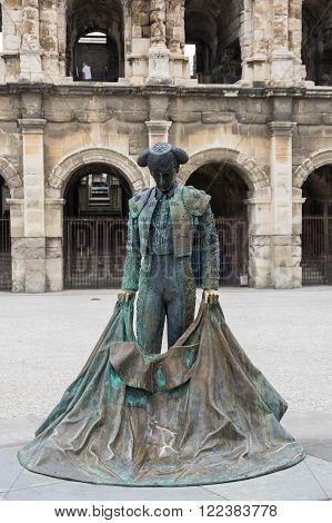 NIMES, FRANCE - MAY 04, 2015: Statue of Toreador and Ancient Roman Theater (Arena) of Nimes, south of France