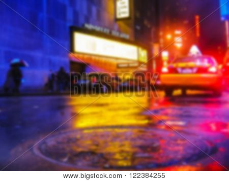 Defocused background with Times Square theater for Broadway shows, city street by night with local taxi and a smoking  manhole, New York, USA. Intentionally blurred post production for bokeh effect.