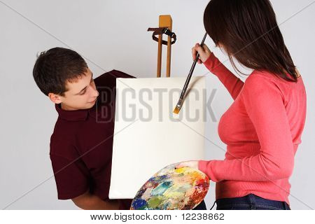 Girl Holding Palette, Painting On Canvas Easel, Man Looking On Picture