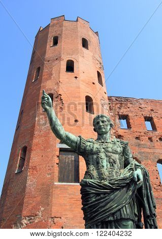 Roman statue of Caesar Augustus and ancient ruins of Palatine Towers in Turin, Italy