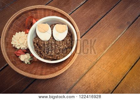 Thai food pound eggplant with boiled egg in white cup and jasmine garland made from soap in Thailand traditional baskets on wood table process in vintage style