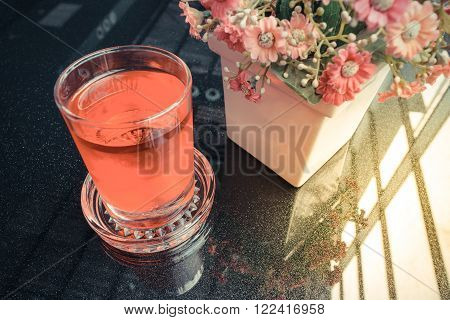 Sweet red water drink in glass and flower on table
