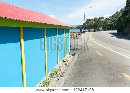 Coastal road past colourful blue and yellow quaint boatshed with red roof.