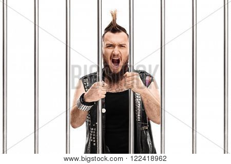Angry punk rocker standing in jail and shouting isolated on white background