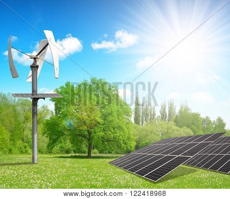 Solar energy panels with wind turbine in spring landscape. Clean energy concept.