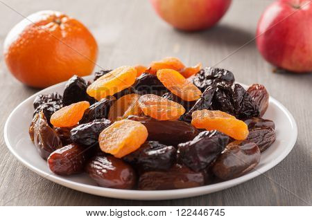 Dried fruits in a white plate on a wooden table with other fruits selective focus