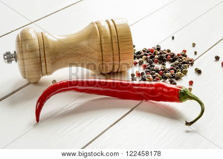 Red hot pepper and pepper mill in the background scattered peas pepper on white wooden table