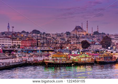 ISTANBUL, TURKEY - OCTOBER 20, 2015: Fisher boats  and mosque in Eminonu District at dawn