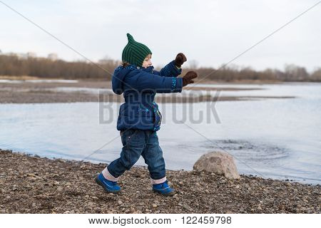 Little girl dancing on a river bank