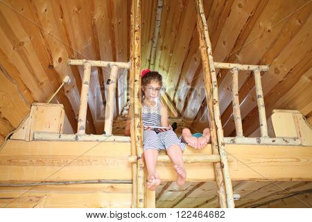 Girl with tablet computer sitting on the bunk next to the other legs in a wooden house