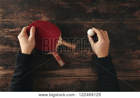 Hands Hold Two Professional Ping Pong Rockets And Ball