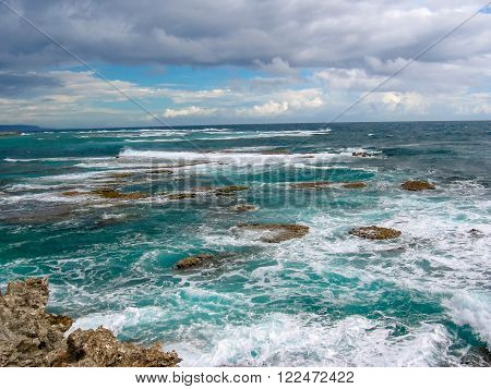 Rocks and strong waves crashing on rocks in the wild north coast of Guadeloupe with cloudy sky, Caribbean, French West Indies.