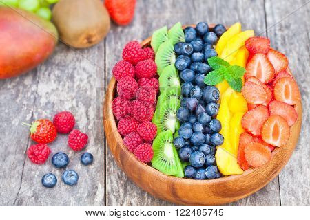 Fresh colorful fruits and berries in wooden bowl on rustic table