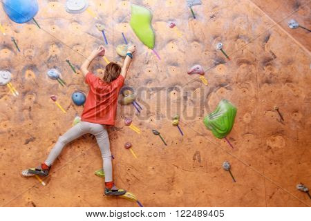 boy climbing on practical wall indoor, bouldering training