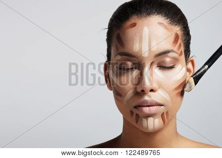 woman with a facial corrector and brush on a face
