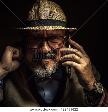 Older person communicating over cell phone, wearing retro style clothes, glasses and hat.