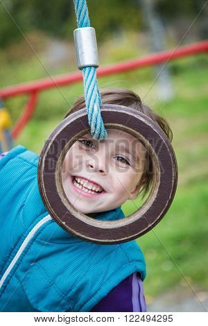 Cute smiling girl on the playground on the sports projectile ring.