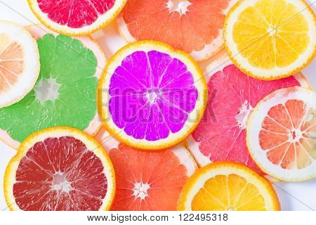 The multi-colored citrus of artificial color cut by circles lies on a table. Orange, lemon, grapefruit. Colors not usual for a citrus. Close up, small depth of sharpness