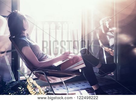 Photo young girl sitting leather armchair in modern building and use laptop wireless internet. Studying at the University, working, preparing exams. Using book, notebook. Relaxing.
