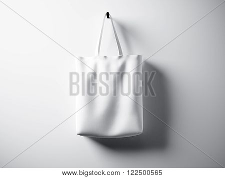 Photo white cotton textile bag hanging left side. Empty white wall background. Highly detailed texture.