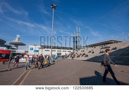 HANNOVER GERMANY - MARCH 14 2016: Attendees have a rest on stairs at CeBIT information technology trade show in Hannover Germany on March 14 2016.