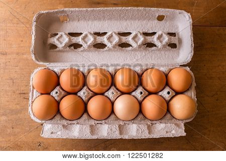 dozen eggs in a cardboard container on a wood table top