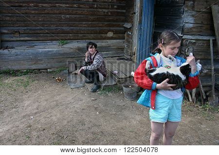 Tver region Russia - May 7 2006: Tanya Girl 11 years old standing near a farm house with a cat in her arms near the porch where her mother was sitting.