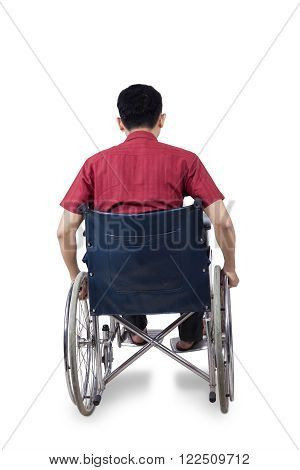 Rear view of disabled person sitting on wheelchair, isolated on white background
