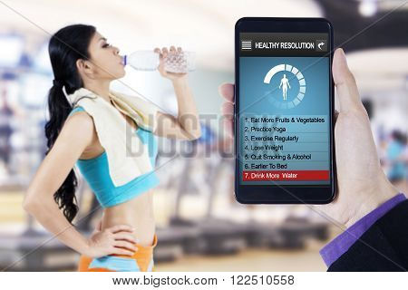 Image of hand holding smartphone with healthy resolutions program on the screen and young woman drinking water at gym