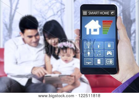 Close up of hand holding mobile phone with smart home applications on the screen and happy family sit on sofa at home