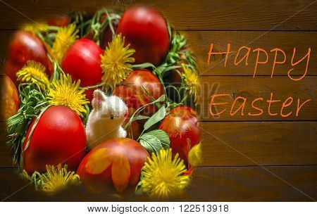 Basket with Easter egs with herbs flowers and bonny at a wodden background as a Happy Easter Card.