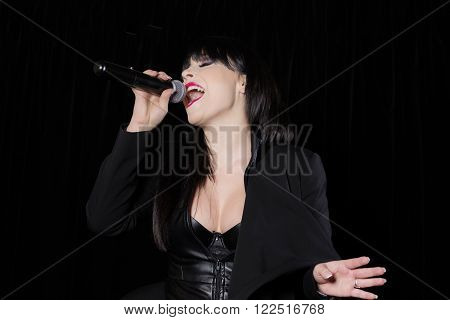 Beautiful singer singing at a microphone on stage on black background