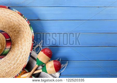 Mexican sombrero and maracas with traditional serape blanket laid on an old blue painted pine wood floor. Space for copy.