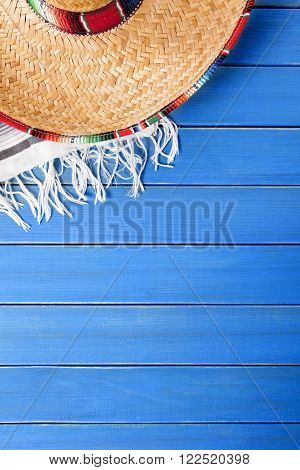 Mexican sombrero with traditional serape blanket laid on an old blue painted pine wood floor. Space for copy.