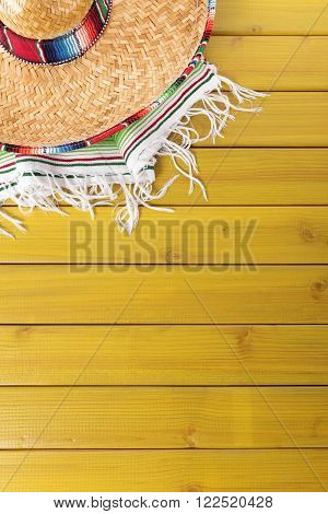 Mexican sombrero and traditional serape blanket laid on a yellow painted pine wood floor. Space for copy.