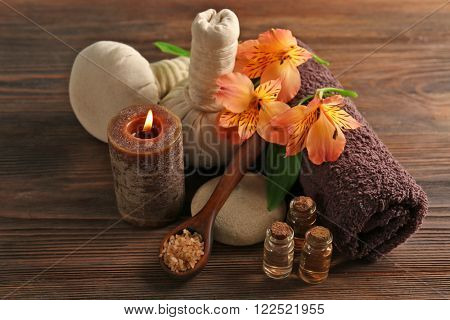 Spa set with sea salt, exotic flowers, candle, massage balls and towel on wooden background