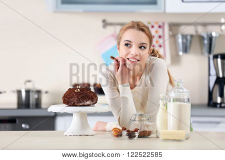 Young woman decorating cake with chocolate