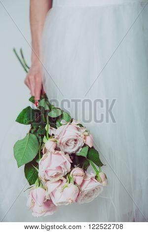 Portrait of a wedding bride posing in a white dress with flowers in her hands. Beautiful wedding bouquet in hands of the bride.
