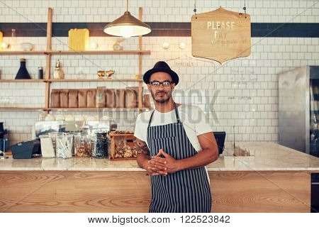 Portrait of a confident young coffee shop owner standing at the cafe counter. Handsome young man working at a restaurant and wearing an apron and hat.