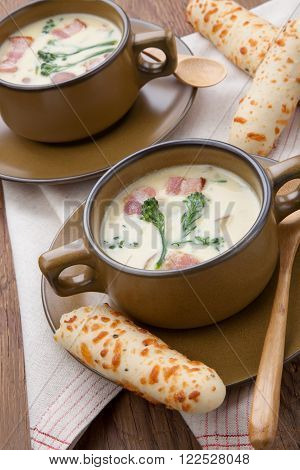 Close up of creamy Broccoli Chowder Soup with beacon, potato, and broccoli. Cheddar rosemary breadsticks.