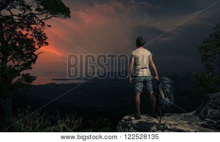 Hiker standing on top of the mountain and watching sunset over the valley
