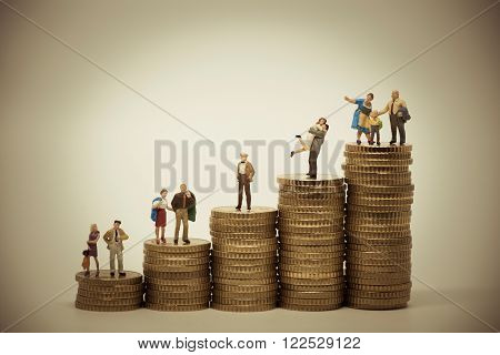 Social scale-concept of various persons in different positions on piles of coins. Vintage color tone
