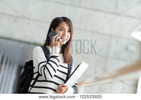 Univeristy student talk to mobile phone with laptop computer