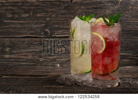 Two summer cocktail with ice mint and lime. Cocktail with white rum or gin and campari cocktail a tumbler glass on a dark wooden background with copy space. Summer cocktails background