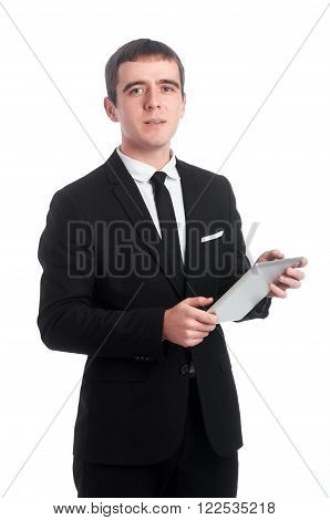Young man in black suit and white shirt with tablet PC in his hands isolated on white background