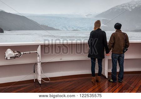 Amilia Glacier, South Patagonia, Chile - December 8, 2012: Couple on board the cruise ship Veendam viewing beautiful glacier. Taken at the Sarmiento Channel, Chile on a overcast rainy day. Amalia Glacier, also known as Skua Glacier, is a tidewater glacier