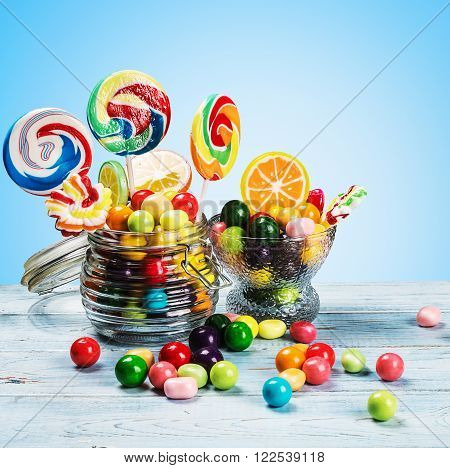 multicolored lollipops candy and chewing gum in glass jar