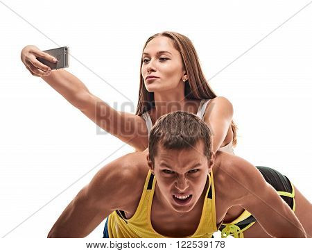 fitness, sport, training, teamwork and lifestyle concept - man starts out push-ups and girl lying on him and makes selfie.